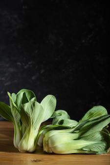 Свежая зеленая китайская капуста на деревянном фоне