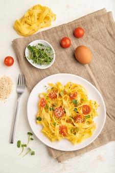 白い木製のテーブルにトマト、卵、ゴマ、マイクログリーンスプラウトのレジーネセモリナパスタ。
