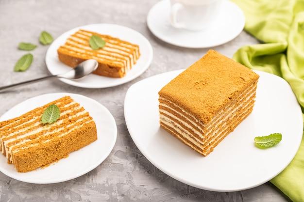 Домашний медовый торт с молочным кремом и мятой с чашкой кофе на сером бетонном столе
