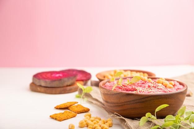 白とピンクのテーブルの上椀でビートとマイクログリーンバジルもやしとフムス