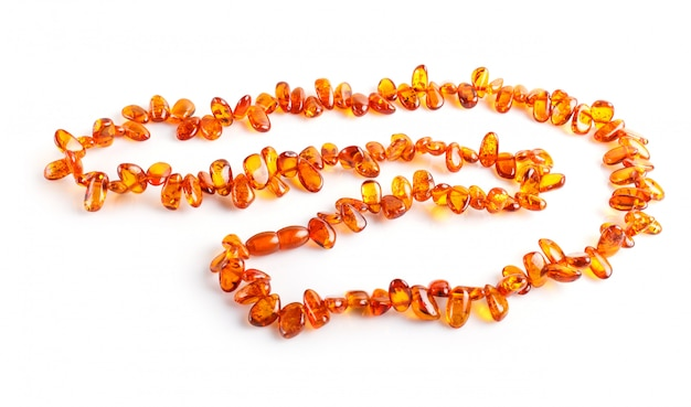Оранжевые янтарные бусы на белом фоне