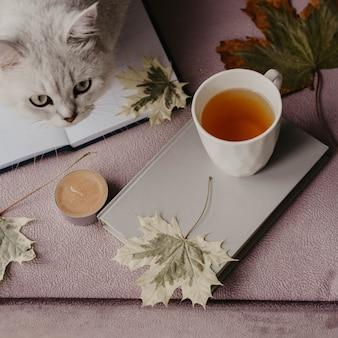 秋の葉のインテリアで本を持つお茶のカップ