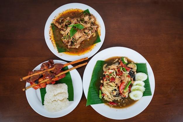 グリルチキン、スパイシーグリルポークサラダ、ナムトクムとグリーンパパイヤサラダ。タイ北東料理。