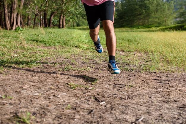 アジア人の男性が日没時に林道を走る