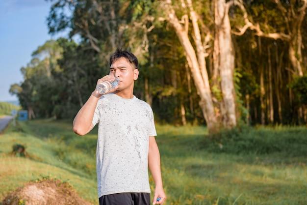 若い男が運動をする前に水を飲む