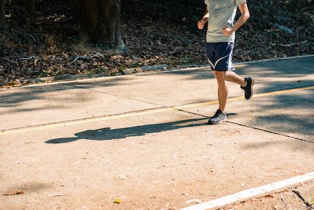 公園の道で走っている若い男ランナーの運動選手