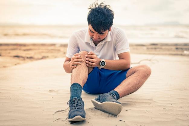 男ランナーはビーチの背景に痛みで彼の膝を保持します。