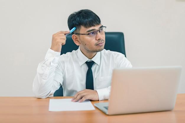 考えて、オフィスで紙とコンピューターのラップトップに書く若い魅力的なビジネスマン