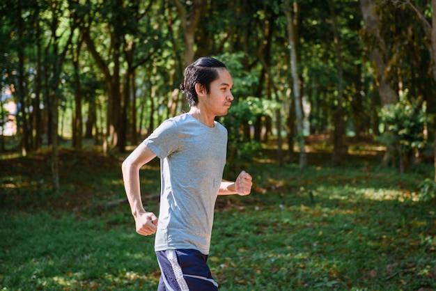 公園を走っている若い男ランナーの運動選手