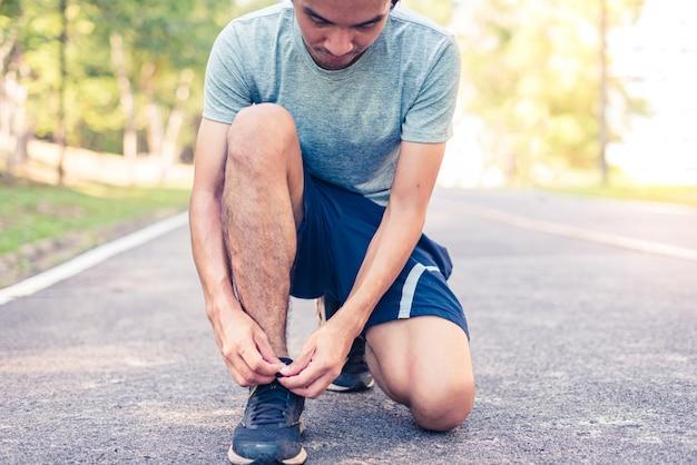 靴ひもを結ぶ男ランナー