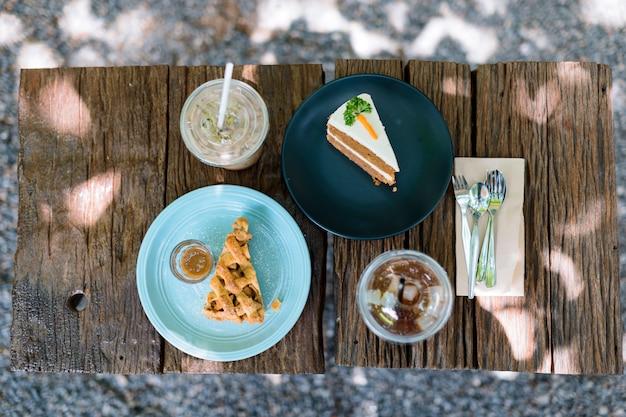 庭の木製テーブルでコーヒーとケーキの午後