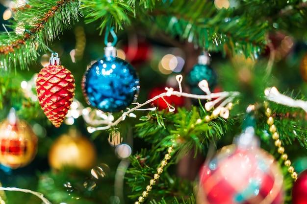光沢のあるクリスマスの装飾用のカラフルな緑のクリスマスツリーに飾られて