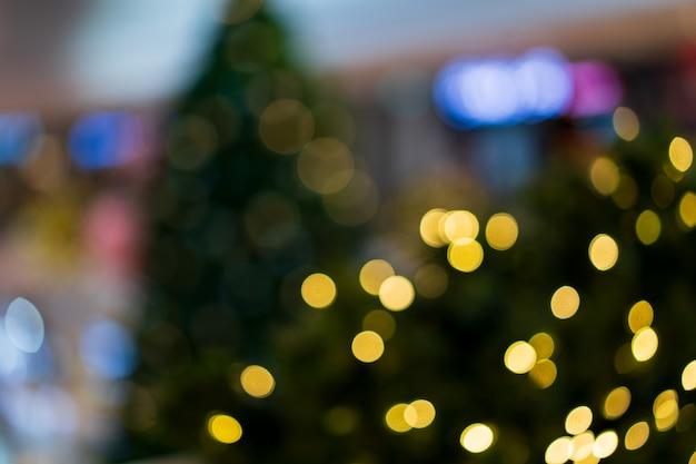 クリスマスの金色の光はパーティー、クリスマスツリーのキラキラとぼやけたライト背景コンセプトを祝います。