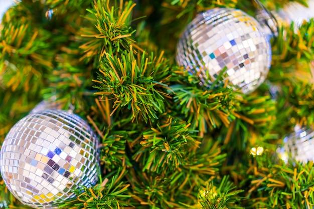 緑の人工的なクリスマスツリーは銀の光沢のあるクリスマスボール、クリスマスの概念で飾る。