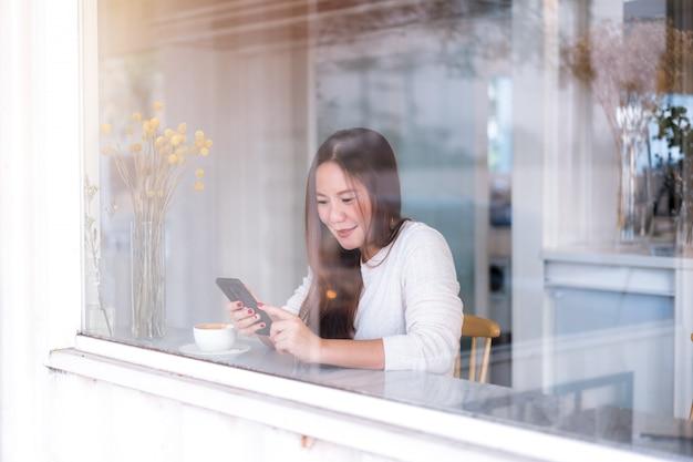 若いアジアの女性は、コーヒーショップのガラス窓から撮影した携帯電話を使用してリラックスします。