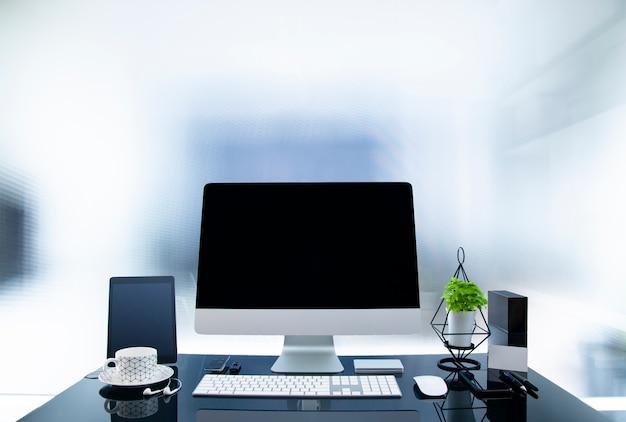 Рабочее место с современным компьютером на стеклянном столе, макет черный экран, комнатное растение и материалы.