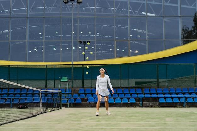 緑の裁判所の芝生の上の女子テニス選手