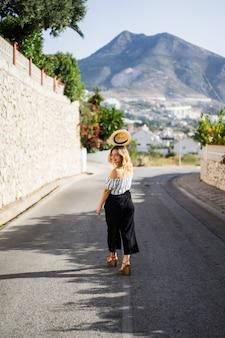 若い美しい女性が小さなヨーロッパの町の通りを通って歩きます。夏休み