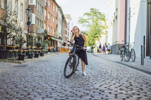 ヨーロッパの都市で自転車に乗る若いスポーツ女性。都市環境におけるスポーツ