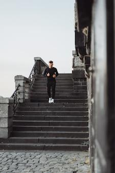 Молодой человек, занятия спортом в европейском городе. спорт в городских условиях.