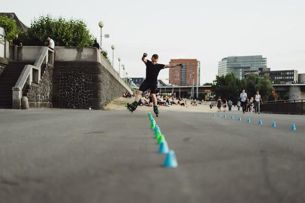 ヨーロッパの都市でローラースケートで若いスポーツ男。都市環境におけるスポーツ