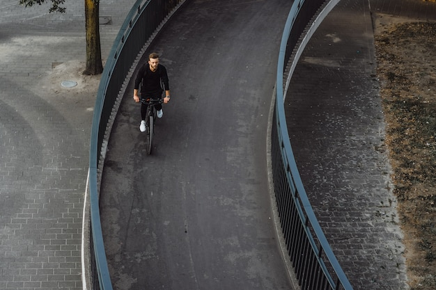 ヨーロッパの都市で自転車に乗って若いスポーツ男。都市環境におけるスポーツ