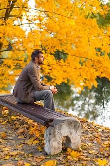 秋の公園を歩いて男