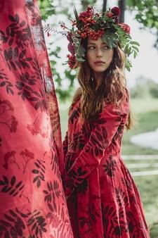 リネンのドレスの少女。彼女の頭に花の花輪を捧げる。