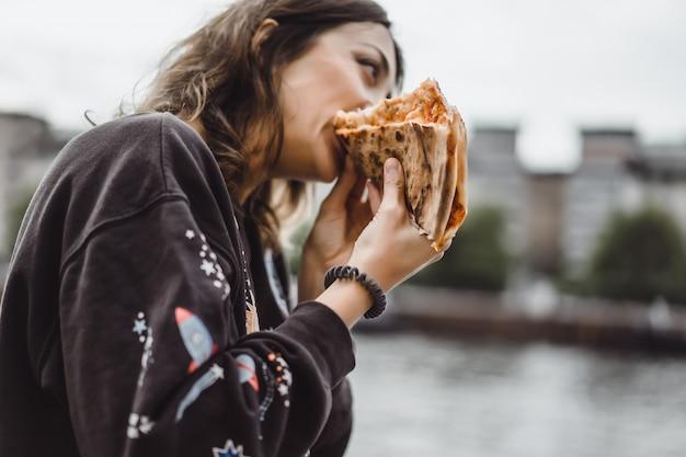Молодая красивая женщина ест кусок пиццы на улице города