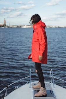 Красивая молодая женщина в красном плаще едет на частной яхте. стокгольм, швеция