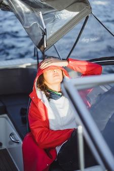 赤いレインコートを着た美しい若い女性は、プライベートヨットに乗る。スウェーデンのストックホルム