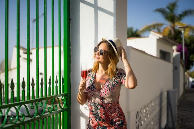 短いドレスを着た若い美しい女性が小さなヨーロッパの町の通りを通って歩きます。夏