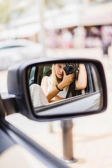 Девушка фотографирует себя в зеркале автомобиля