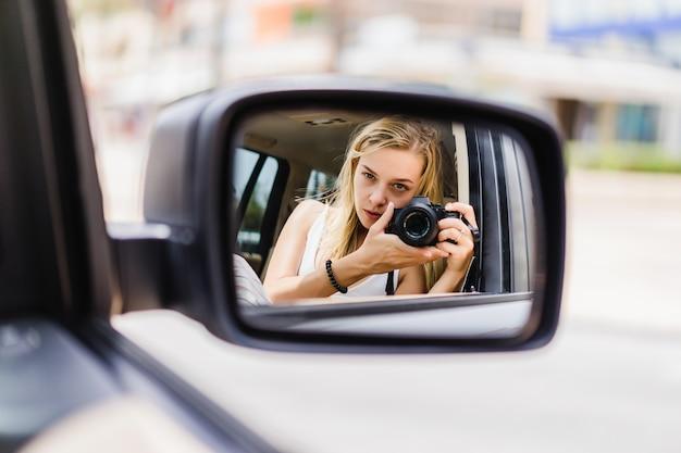 女の子が車のミラーで自分の写真を撮る