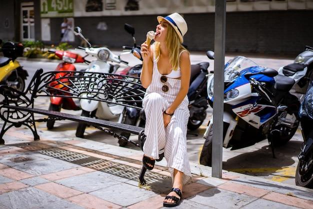 暑い日にワッフルコーンでアイスクリームを食べる若い女性