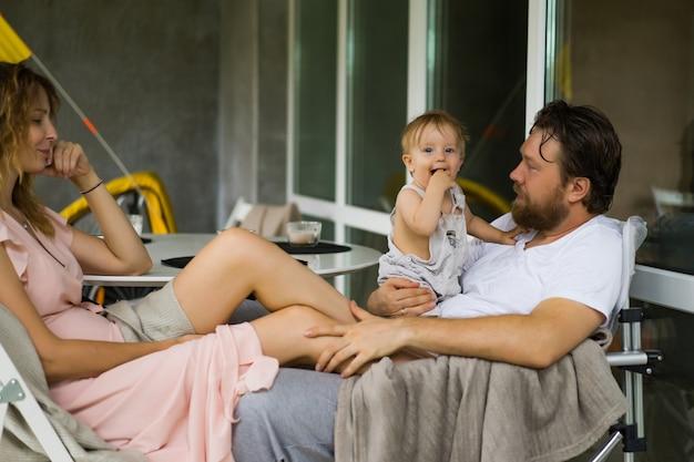 Молодая влюбленная пара с маленьким ребенком на террасе своего дома.