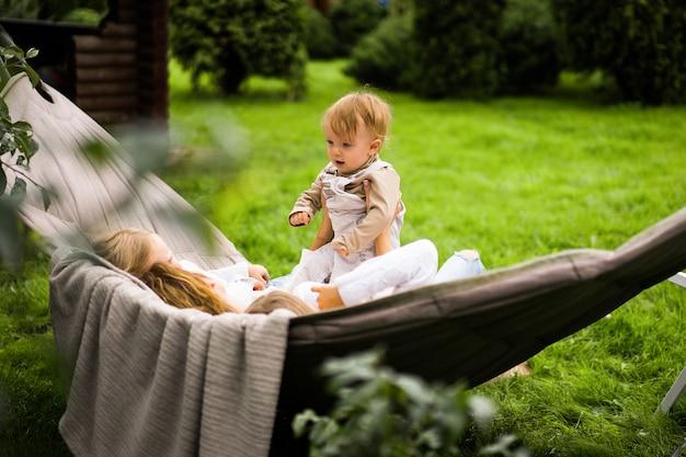 ハンモックで楽しんでいる子供を持つ母。ママと子供たちがハンモックで。