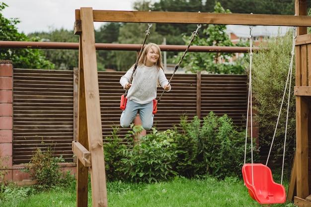 ブランコに乗っている子供たち。女の子が庭のブランコに揺れています。夏のお楽しみ。