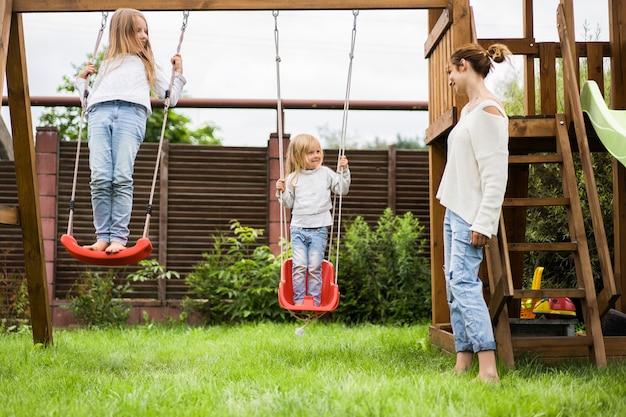 ブランコに乗っている子供たち。女の子の姉妹は庭のブランコに揺れています。夏のお楽しみ。