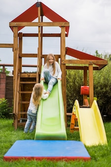 Дети катаются с детской горки, сестры играют вместе в саду