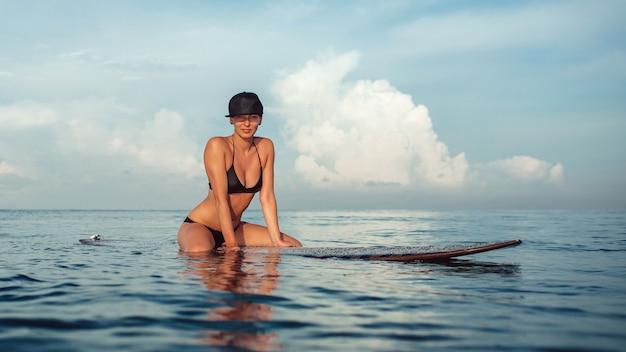 海のサーフボードの上に座ってポーズ美しい少女