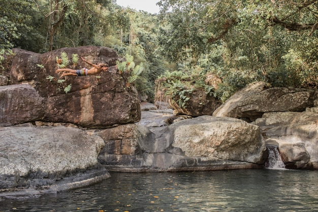 男は石から水の中に飛びます
