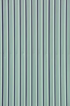 フェンスの壁、垂直線とのシームレスな抽象的な背景として灰色緑亜鉛めっき鋼板