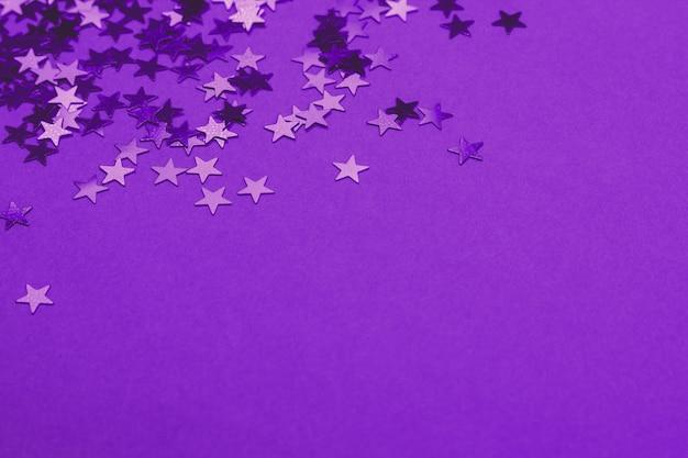 星型の紙吹雪と美しい祭りの紫色の背景。休日や装飾