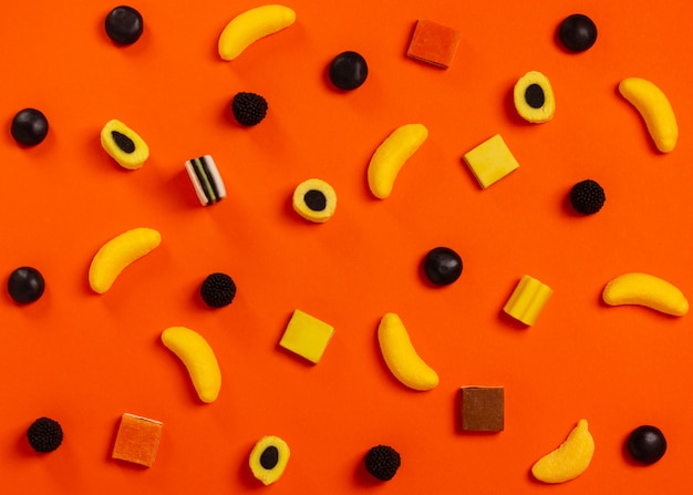 オレンジ色の背景にスタイリッシュなカラフルなキャンデーパターン。上面図。フラットレイ。あなたのための背景