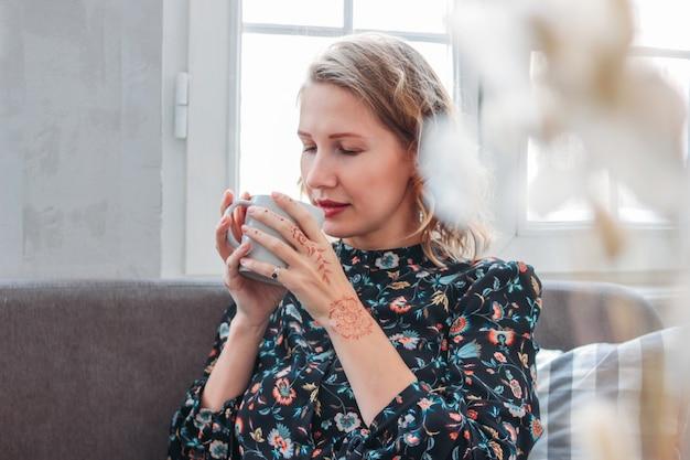 ソファの上に座ってお茶のカップとドレスの美しいロマンチックな若いブロンドの女性