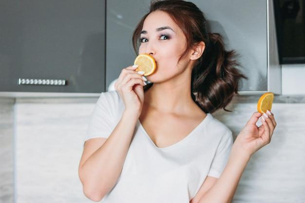 Счастливая усмехаясь красивая молодая девушка азиатских длинных волос смешная с лимоном в кухне