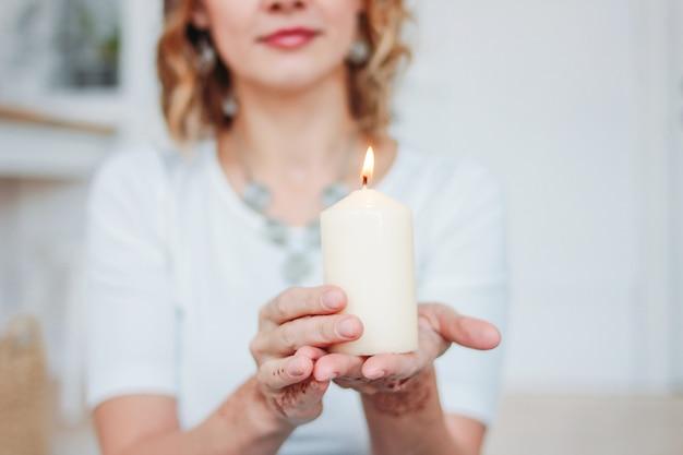 Белокурая молодая женщина в белой одежде с мехенди держит горящую свечу