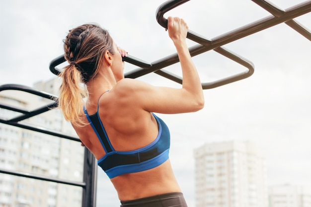 スポーツウェアの少女の魅力的なフィットの若い女性は、ストリートトレーニングエリアでバーにプルアップします。