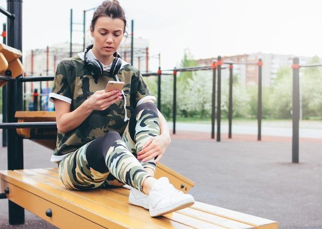 ストリートトレーニングエリアで携帯電話でトレーニングを行う軍事色のスポーツウェアの魅力的なフィットの若い女性。